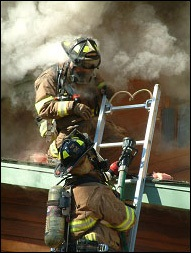 photo of firefighters climbing from ladder onto burning house