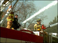 photo of firefighters spraying water from a fire truck