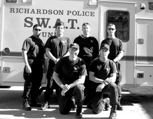 Photo of SWAT Team posed in front of vehicle