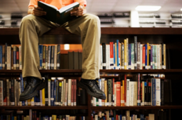image of teen sitting on bookshelf