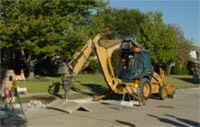photo of digger breaking concrete for street repair
