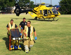 photo of EMS personnel taking cart from helicopter